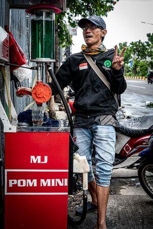 質素な給油所でバイクに軽油を給油していた男