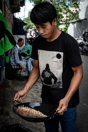 Young man shaking a wok