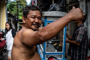 Shirtless man raising his arm up in front of a food stall