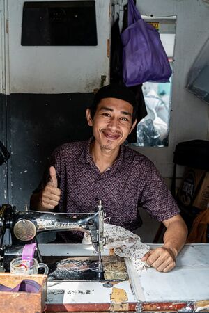 Young tailor working with an old sewing machine