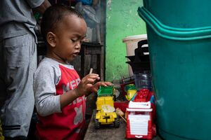 Little boy playing with working car toys