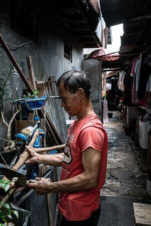 路地の入り口で木材を手にしていた男