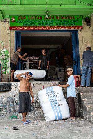 Men working around big bags