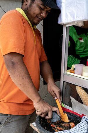すり鉢でスパイスを潰す男