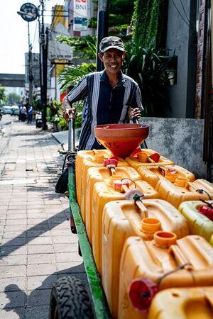 Man carrying polyethylene tanks