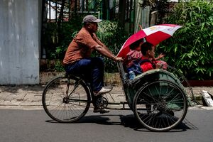 Becak driving through the streets of Jakarta