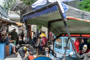 Becak, food stall, and people on the side of the road