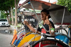 Becak driver thumbing up strongly