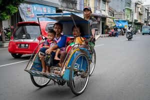 Becak running with parents and children