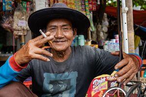 煙草を燻らす帽子かぶったベチャの運転手