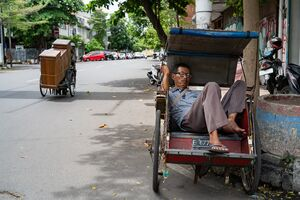 Man taking a nap on a Becak