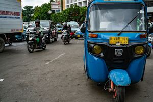 Bajaj parked on the side of a busy road