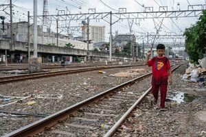 Boy walking beside the railroad tracks, thinking