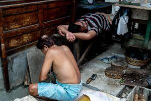 Man squatting and man lying down