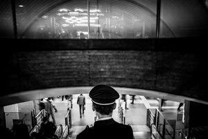 エスカレータに乗った制服を来た渋谷駅員