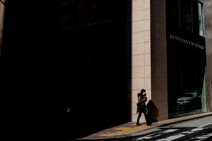 影の落ちたビルの角を歩く女性