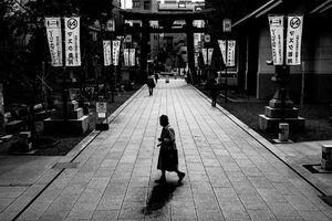 Old woman crossing the approach to Tomioka Hachimangu Shrine