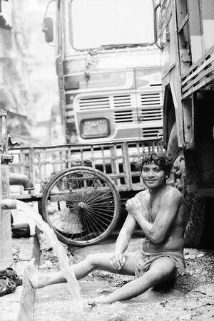 道端で体を洗う男