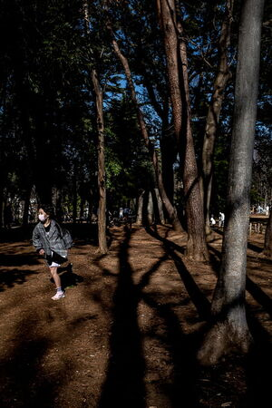 Girl running through a grove of trees