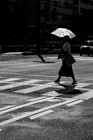 日傘を差して道を渡る女