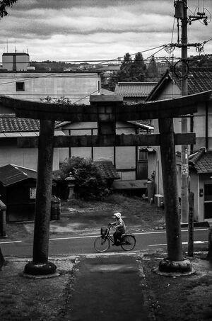 Bicycle passing by the torii of Tsuruyama Hachiman-Gu
