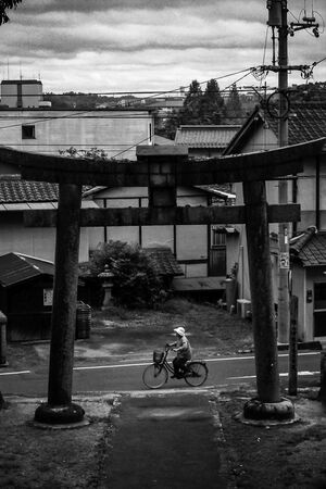 Older woman riding bicycle in front of Torii