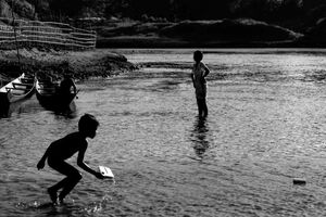 Silhouetted kids playing in river