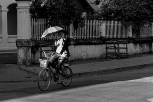 Woman riding bicycle with sunshade