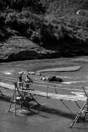 竹製の橋の上で立ち話をする僧侶