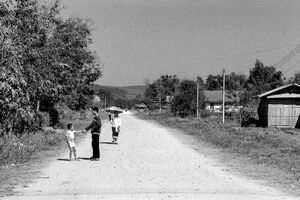 Two boys and one woman on dirt road