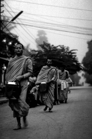 Buddhist monks walking dim street to ask fro alms