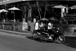 Women putting sunshade up while riding motorbike