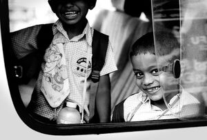 Two boys looking through car window