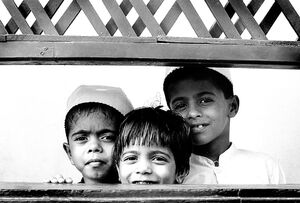 Three kids on the other side of the fence