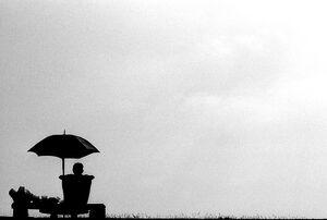 日傘の下で寛ぐシルエットになった男