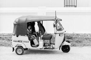 Woman sitting on rear seat of three wheeler