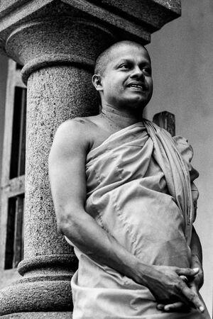 Buddhist monk leaning against pillar