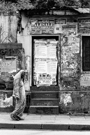 Woman with a saree in front of boarded-up door