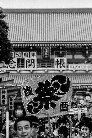 浅草寺境内の人混みの中に見える大きな団扇