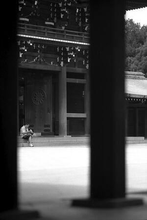 Man sitting in front of gate in Meiji Jingu