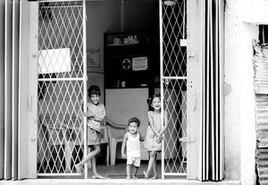 Three kids standing at gate