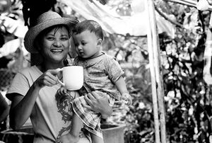 Mother holding mug and baby
