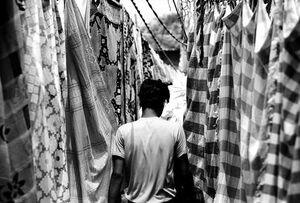 洗濯物の間を歩く男