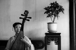 Woman playing Chinese lute with deadpan face
