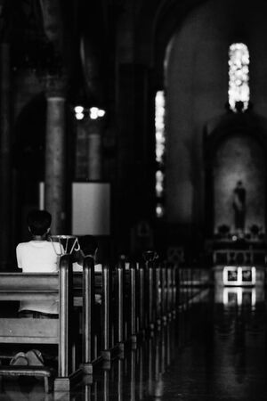 Worshiper in dim Manila cathedral