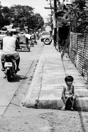 Girl sitting on sidewalk alone