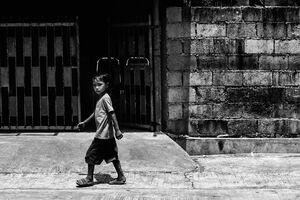 強い日差しの中を歩く男の子