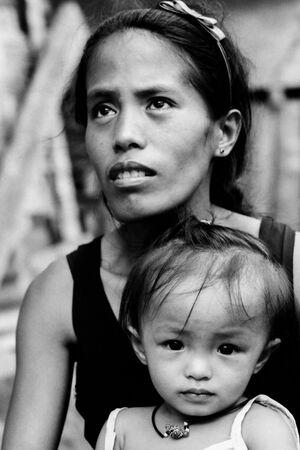 Little girl sitting on mother's knee