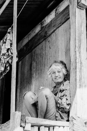 Woman with silver hair sitting under eaves