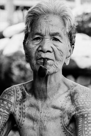 Tattooed older woman puffing on pipe